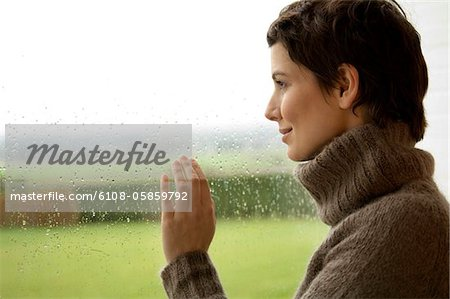 Mid adult woman looking out through a window Stock Photo - Premium Royalty-Free, Image code: 6108-05859792