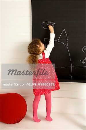 Girl drawing on a blackboard Stock Photo - Premium Royalty-Free, Image code: 6108-05860226