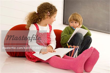 Boy and a girl drawing on notepads Stock Photo - Premium Royalty-Free, Image code: 6108-05860236