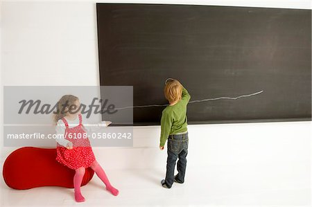 Rear view of a boy drawing on a blackboard with his sister sitting beside him Stock Photo - Premium Royalty-Free, Image code: 6108-05860242