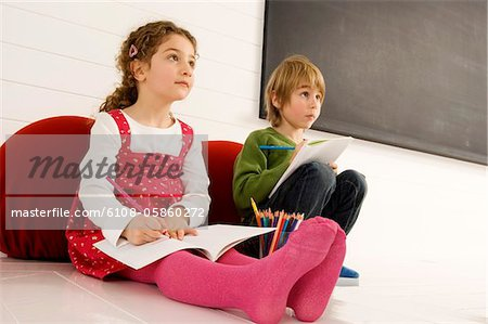 Boy and a girl drawing on notepads Stock Photo - Premium Royalty-Free, Image code: 6108-05860272