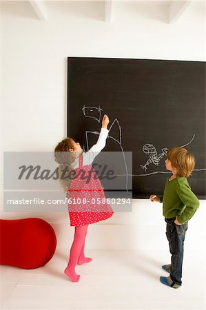 Girl drawing on a blackboard and her brother watching her Stock Photo - Premium Royalty-Free, Image code: 6108-05860294