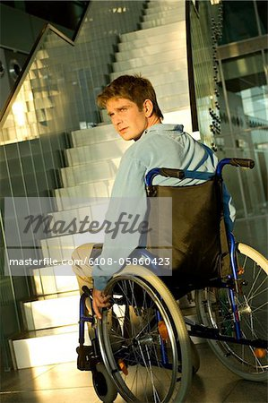 Mid adult man sitting in a wheelchair Stock Photo - Premium Royalty-Free, Image code: 6108-05860423