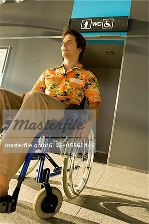 Mid adult man sitting in a wheelchair in front of a restroom entrance Stock Photo - Premium Royalty-Free, Image code: 6108-05860446