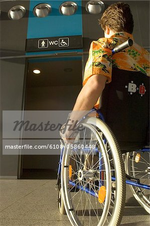 Rear view of a mid adult man sitting in a wheelchair Stock Photo - Premium Royalty-Free, Image code: 6108-05860448