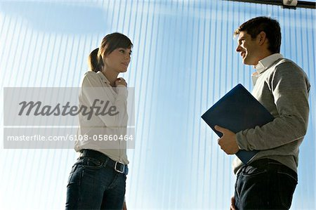 Side profile of a businessman holding a laptop and talking to a businesswoman Stock Photo - Premium Royalty-Free, Image code: 6108-05860464