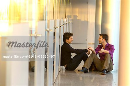 Two businessmen sitting in a corridor and talking with each other Stock Photo - Premium Royalty-Free, Image code: 6108-05860497