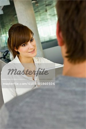 Young woman using a laptop and looking at a mid adult man Stock Photo - Premium Royalty-Free, Image code: 6108-05860506