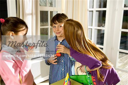 Girl kissing a boy and her friend looking at them Stock Photo - Premium Royalty-Free, Image code: 6108-05860634