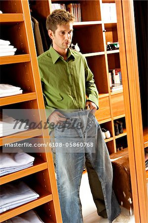 Reflection of a mid adult man getting dressed Stock Photo - Premium Royalty-Free, Image code: 6108-05860768