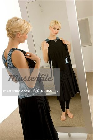 Young woman trying on a dress in front of a mirror Stock Photo - Premium Royalty-Free, Image code: 6108-05860817