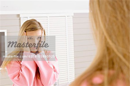 Reflection of a young woman in a mirror looking sad Stock Photo - Premium Royalty-Free, Image code: 6108-05860925