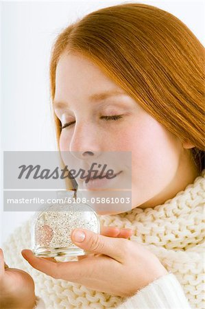 Close-up of a young woman smelling perfume from a bottle Stock Photo - Premium Royalty-Free, Image code: 6108-05861003