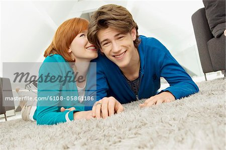 Portrait of a young woman whispering to a teenage boy Stock Photo - Premium Royalty-Free, Image code: 6108-05861186