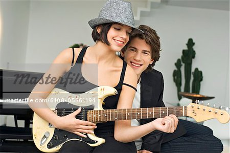 Young woman playing a guitar with a teenage boy leaning beside her Stock Photo - Premium Royalty-Free, Image code: 6108-05861194