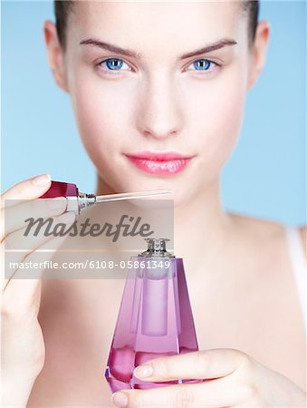 Young woman smelling perfume Stock Photo - Premium Royalty-Free, Image code: 6108-05861349
