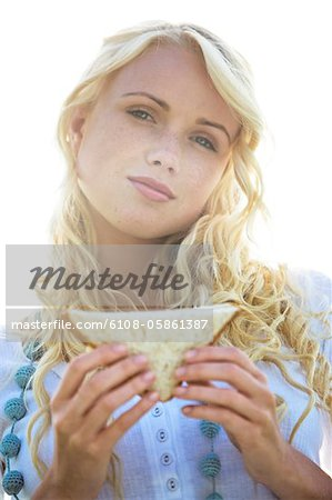 Young woman holding a sandwich Stock Photo - Premium Royalty-Free, Image code: 6108-05861387