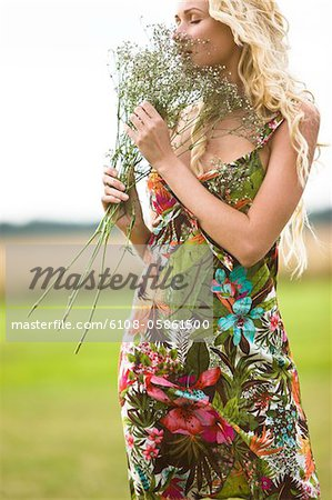 Young woman holding bunch of flowers Stock Photo - Premium Royalty-Free, Image code: 6108-05861500
