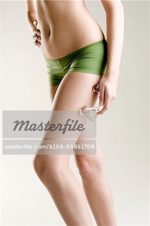 Woman massaging her leg with a massager Stock Photo - Premium Royalty-Free, Image code: 6108-05861708