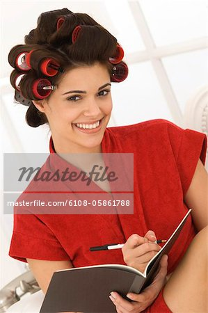 Woman writing in a notebook Stock Photo - Premium Royalty-Free, Image code: 6108-05861788