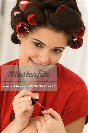 Close-up of a woman painting finger nails Stock Photo - Premium Royalty-Free, Image code: 6108-05862284
