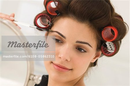 Close-up of a woman tweezing eyebrows Stock Photo - Premium Royalty-Free, Image code: 6108-05862310
