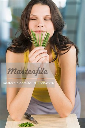 Woman smelling chives Stock Photo - Premium Royalty-Free, Image code: 6108-05862394