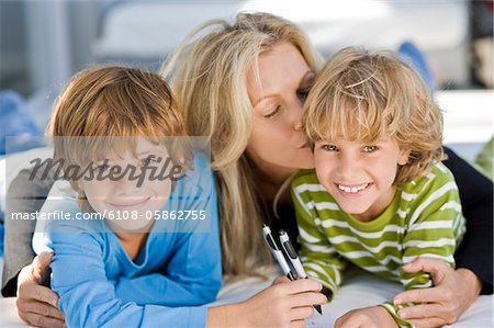 Portrait of two boys smiling with their mother Stock Photo - Premium Royalty-Free, Image code: 6108-05862755