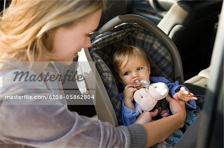 Woman fastening her son on a baby seat in a car Stock Photo - Premium Royalty-Free, Image code: 6108-05862804