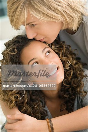 Teenage boy kissing on the forehead of a girl