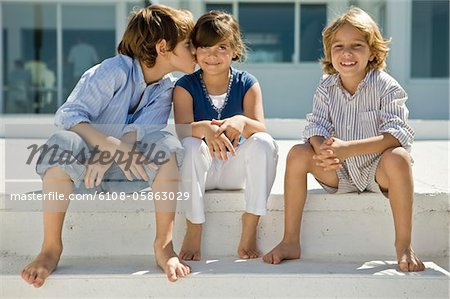Boy kissing a girl with his friend sitting beside them Stock Photo - Premium Royalty-Free, Image code: 6108-05863029