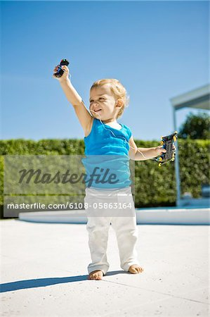 Baby boy holding a remote controlled car and smiling Stock Photo - Premium Royalty-Free, Image code: 6108-05863164