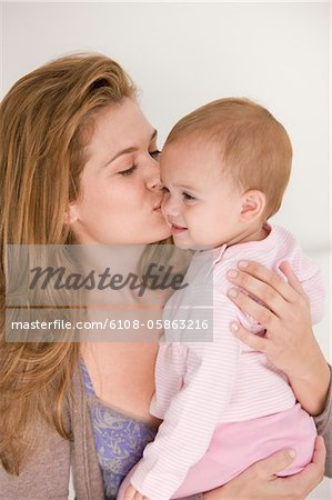 Woman kissing her daughter Stock Photo - Premium Royalty-Free, Image code: 6108-05863216