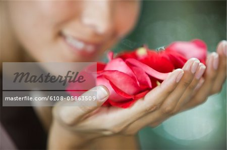 Woman smelling rose flowers Stock Photo - Premium Royalty-Free, Image code: 6108-05863509