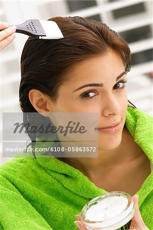 Portrait of a woman applying hair color in her hair Stock Photo - Premium Royalty-Free, Image code: 6108-05863572