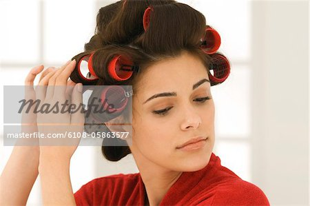 Woman adjusting curlers in her hair Stock Photo - Premium Royalty-Free, Image code: 6108-05863577