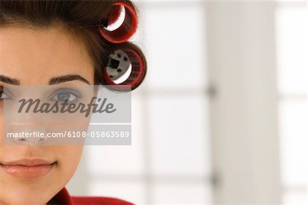 Portrait of a woman with hair curlers in her hair Stock Photo - Premium Royalty-Free, Image code: 6108-05863589