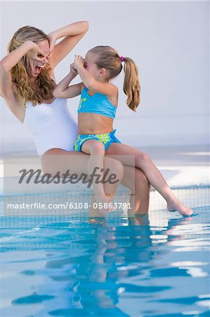 Girl taking a picture of her mother Stock Photo - Premium Royalty-Free, Image code: 6108-05863791
