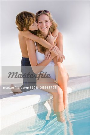 Boy hugging his mother at the poolside and smiling Stock Photo - Premium Royalty-Free, Image code: 6108-05863793