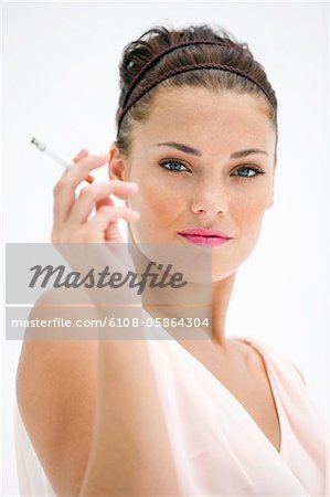 Portrait of a woman smoking a cigarette Stock Photo - Premium Royalty-Free, Image code: 6108-05864304