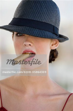 Fashion model smoking a cigar Stock Photo - Premium Royalty-Free, Image code: 6108-05864309