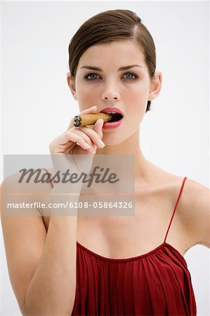 Fashion model smoking a cigar Stock Photo - Premium Royalty-Free, Image code: 6108-05864326