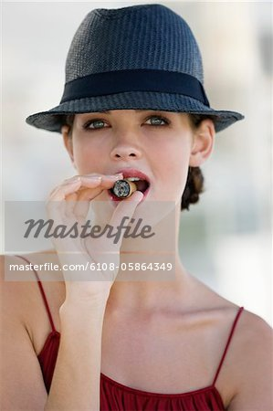 Fashion model smoking a cigar Stock Photo - Premium Royalty-Free, Image code: 6108-05864349