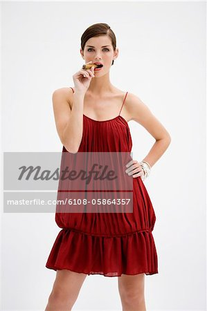 Fashion model smoking a cigar Stock Photo - Premium Royalty-Free, Image code: 6108-05864357