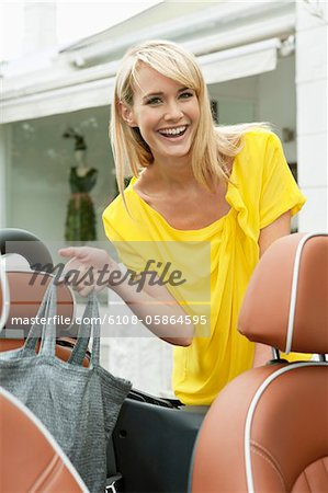 Woman smiling near a car after shopping Stock Photo - Premium Royalty-Free, Image code: 6108-05864595