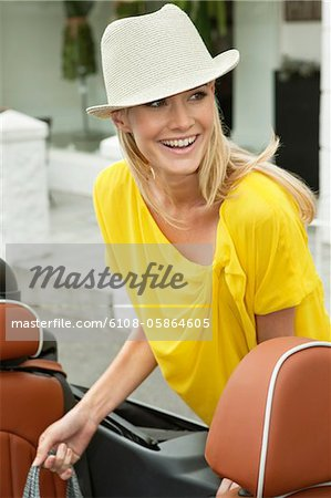 Woman smiling near a car after shopping Stock Photo - Premium Royalty-Free, Image code: 6108-05864605