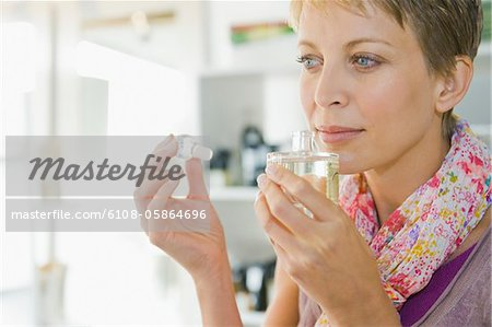 Woman smelling perfume in a store Stock Photo - Premium Royalty-Free, Image code: 6108-05864696