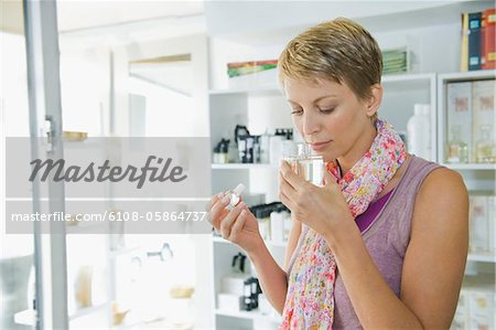 Woman smelling perfume in a store Stock Photo - Premium Royalty-Free, Image code: 6108-05864737