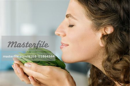 Woman smelling spinach leaves in the kitchen Stock Photo - Premium Royalty-Free, Image code: 6108-05864944