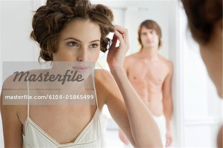 Woman using curlers with her boyfriend in the background Stock Photo - Premium Royalty-Free, Image code: 6108-05865499